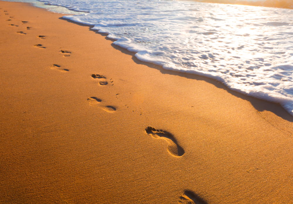 footprints in the sand near ocean